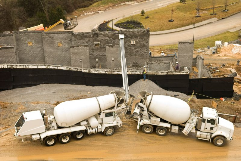Concrete being poured by two vehicles on a construction site.